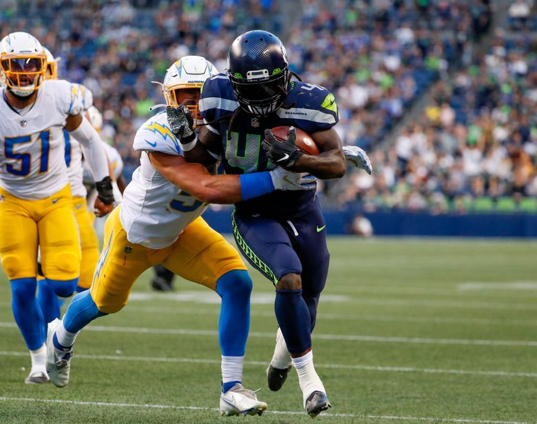 Seattle Seahawks running back Alex Collins tries to push past Los Angeles Chargers linebacker Cole Christiansen  during the first quarter Saturday. (Jennifer Buchanan / The Seattle Times)