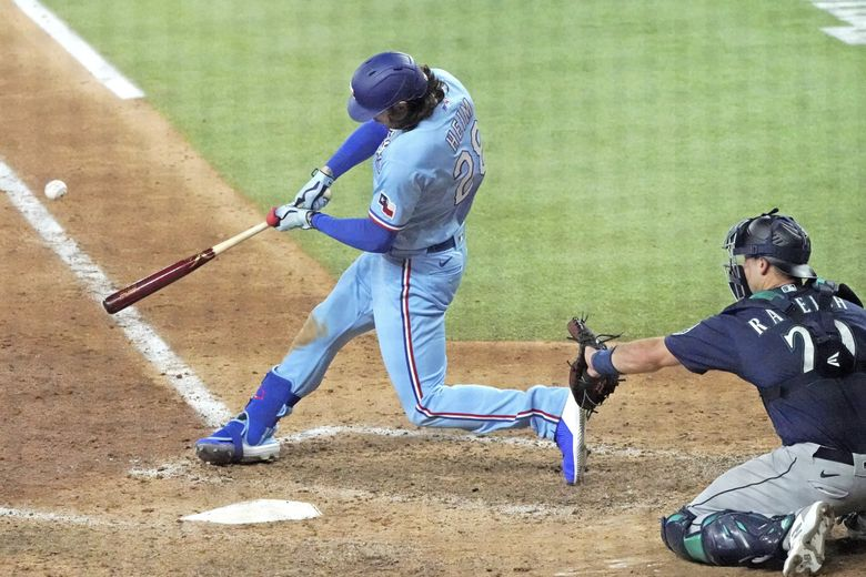 Texas Rangers designated hitter Jonah Heim hits a winning home run against the Seattle Mariners in the ninth inning Sunday. (Louis DeLuca / The Associated Press)