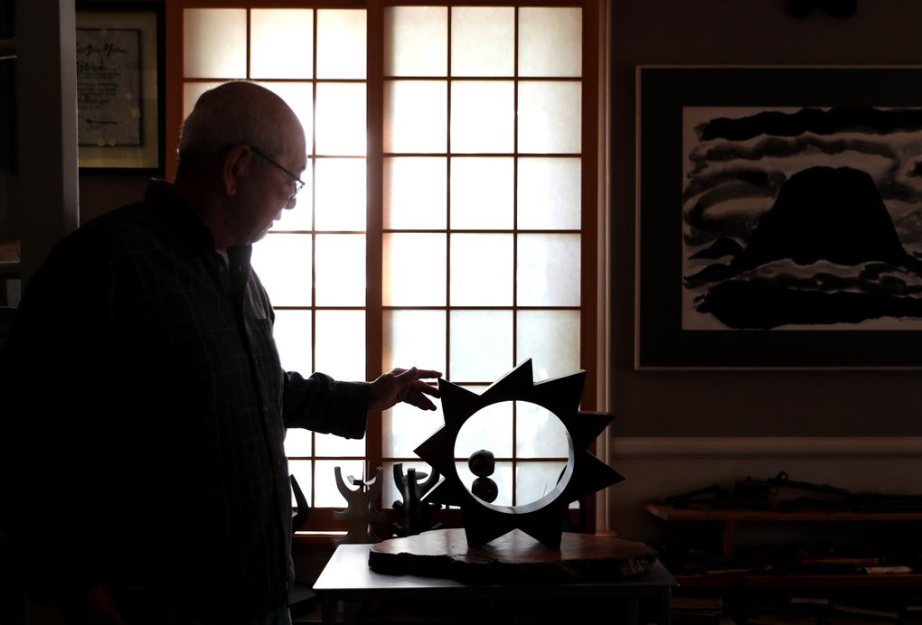 """Gerard Tsutakawa touches one of his bronze pieces, 2017's """"Sun Circle,"""" in his study in Seattle last month. Tsutakawa is inspired by the abstraction of nature in his sculptures. (Ken Lambert / The Seattle Times)"""