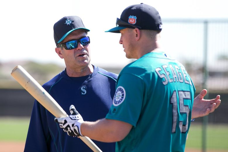 In this file photo from 2016, hitting coach Edgar Martinez talks with Kyle Seager as the full squad reports for  Seattle Mariners spring training in Peoria, Arizona. (Bettina Hansen / The Seattle Times)