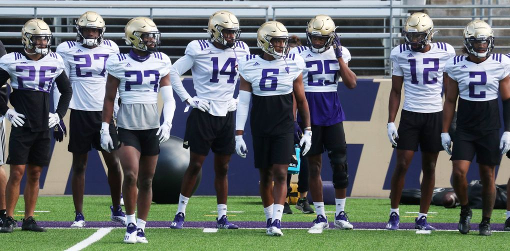 Defensive players, including defensive back Cameron Williams (6) who had two interceptions, wait for the next drill during University of Washington football practice, Sunday, Aug. 8, 2021 in Seattle. This is UW football camp day 3. (Ken Lambert / The Seattle Times)