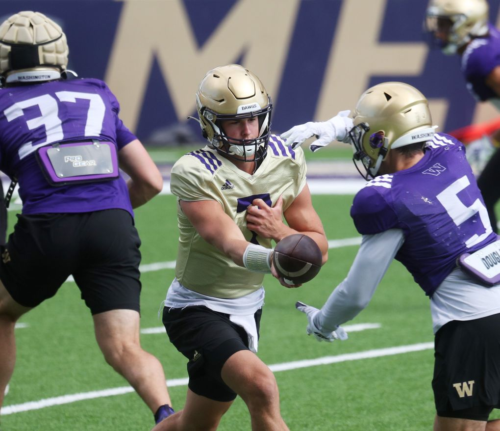 Quarterback Sam Huard (7) runs a drill, handing off to tailback Sean McGrew (5) during University of Washington football practice, Sunday, Aug. 8, 2021 in Seattle. This is UW football camp day 3.  (Ken Lambert / The Seattle Times)