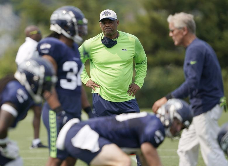 Seattle Seahawks defensive coordinator Ken Norton Jr., center, stands near head coach Pete Carroll, right, as they watch NFL football practice Tuesday, Aug. 3, 2021, in Renton, Wash.  (Ted S. Warren / The Associated Press)