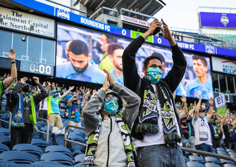 Sounders fans welcome their team on to the pitch in May. (Dean Rutz / The Seattle Times)