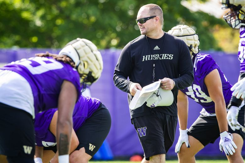 Offensive line coach Scott Huff works with his unit during fall camp at the University of Washington's Husky Stadium in Seattle Sunday August 15, 2021. (Bettina Hansen / The Seattle Times)