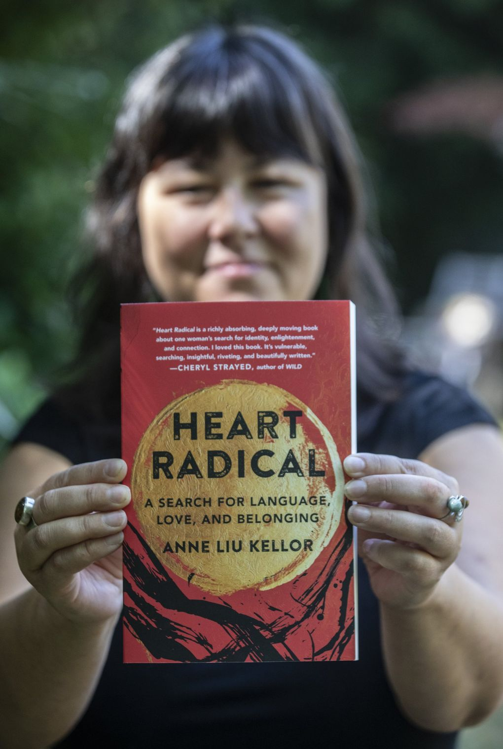 """Anne Liu Kellor shows off her debut memoir """"Heart Radical: A Search for Language, Love, and Belonging"""" Aug. 24, 2021, in North Seattle.   (Steve Ringman / The Seattle Times)"""