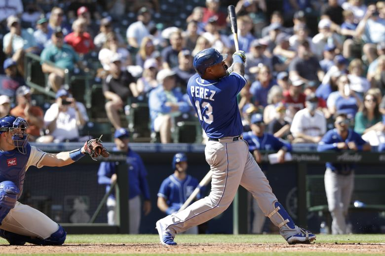 Kansas City Royals' Salvador Perez (13) hits a home run as Seattle Mariners catcher Cal Raleigh, left, looks on during the sixth inning Sunday. (Jason Redmond / The Associated Press)