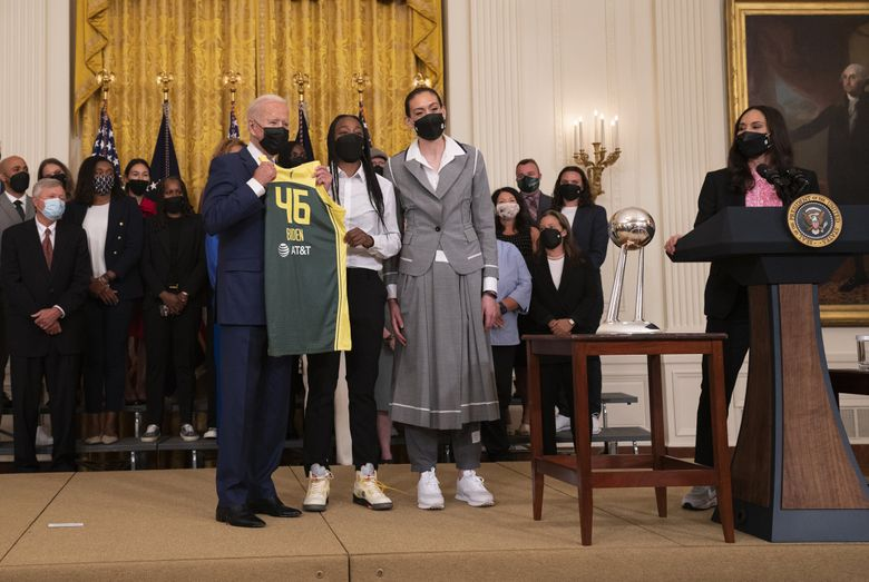 Storm players Jewell Loyd, center, and Breanna Stewart present a No. 46 jersey to President Joe Biden on Monday during a White House ceremony celebrating their 2020 WNBA championship. (Melissa Lyttle / for The Seattle Times)