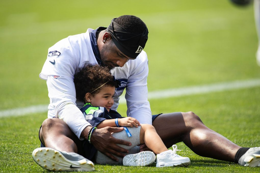 Quandre Diggs cuddles his daughter, Ariya Marie, after practice Monday. The Seattle Seahawks practiced Monday, August 2, 2021 at the VMAC in Renton, WA.. (Dean Rutz / The Seattle Times)
