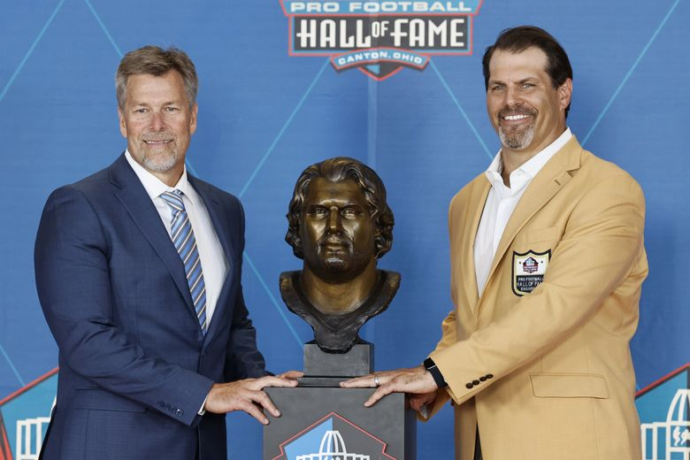Steve Hutchinson, right, a member of the Pro Football Hall of Fame Centennial Class, poses with his presenter, Robbie Tobeck, during the induction ceremony at the Pro Football Hall of Fame, Saturday. (Ron Schwane / The Associated Press)