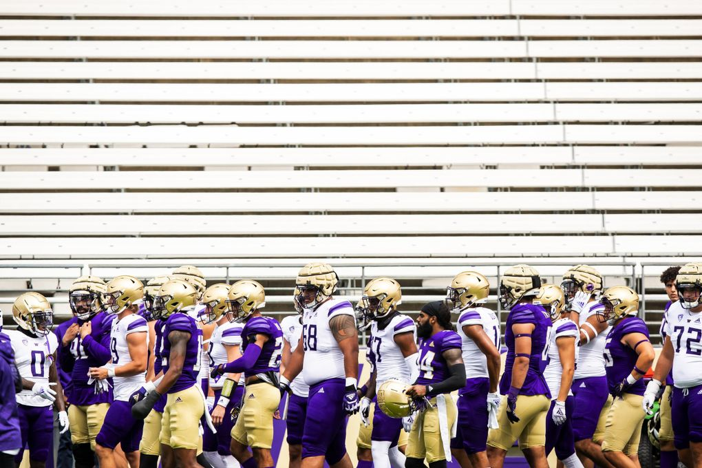 Players walk off the field after warming up for a scrimmage as part of fall camp at Husky Stadium in Seattle, Aug. 21, 2021. (Bettina Hansen / The Seattle Times)