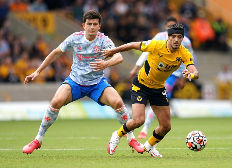 Wolverhampton Wanderers' Raul Jimenez, right, and Manchester United's Harry Maguire battle for the ball during the English Premier League soccer match between Wolverhampton Wanderers and Manchester United at Molineux Stadium, Wolverhampton, England, Sunday, Aug. 29, 2021. (Nick Potts/PA via AP)