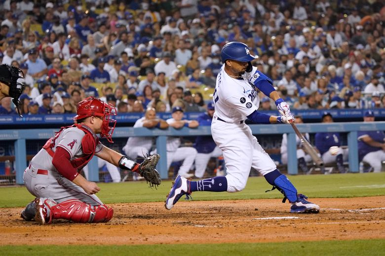 Los Angeles Dodgers' Mookie Betts drives in a run with a single during the fourth inning of the team's baseball game against the Los Angeles Angels on Friday, Aug. 6, 2021, in Los Angeles. (AP Photo/Marcio Jose Sanchez)