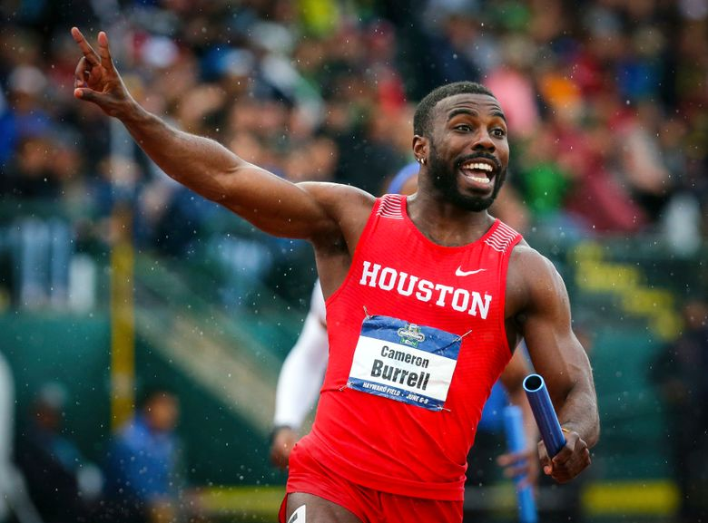 FILE – In this June 8, 2018 file photo, Houston's Cameron Burrell raises two fingers to indicate Houston's back-to-back men's 400-meter relay wins, during the third day of the NCAA Outdoor Track and Field Championships at Hayward Field in Eugene, Ore.   Burrell, the former NCAA national champion sprinter died on Monday, Aug. 9, 2021 according to the University of Houston, where he starred from 2013-2018. (Andy Nelson/The Register-Guard via AP, File)