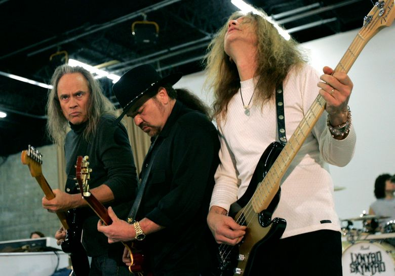 FILE – In this Friday, Feb. 4, 2005 file photo, Members of Lynyrd Skynyrd, from left, Rickey Medlocke, Gary Rossington and Ean Evans, practice at the Jacksonville Production Studio in Jacksonville, Fla. for their Saturday performance as part of the Super Bowl concert series. Lynyrd Skynyrd has pulled out of the Pro Football Hall of Fame concert after guitarist Rickey Medlocke tested positive for COVID-19, Saturday, Aug. 7, 2021. The band was set to co-headline the concert Monday night with Brad Paisley. According to a band statement, Medlocke's positive test forced the group's withdrawal. (AP Photo/Ann Heisenfelt, File)