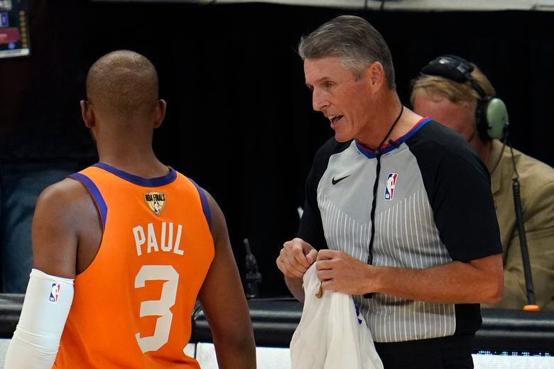 FILE – In this Tuesday, July 20, 2021, file photo, referee Scott Foster talks with Phoenix Suns guard Chris Paul (3) before the start of Game 6 of basketball's NBA Finals against the Milwaukee Bucks in Milwaukee. The NBA said Saturday, Aug. 28, 2021, that its referees have all agreed to be vaccinated as a condition for working games this season. (AP Photo/Paul Sancya, File)