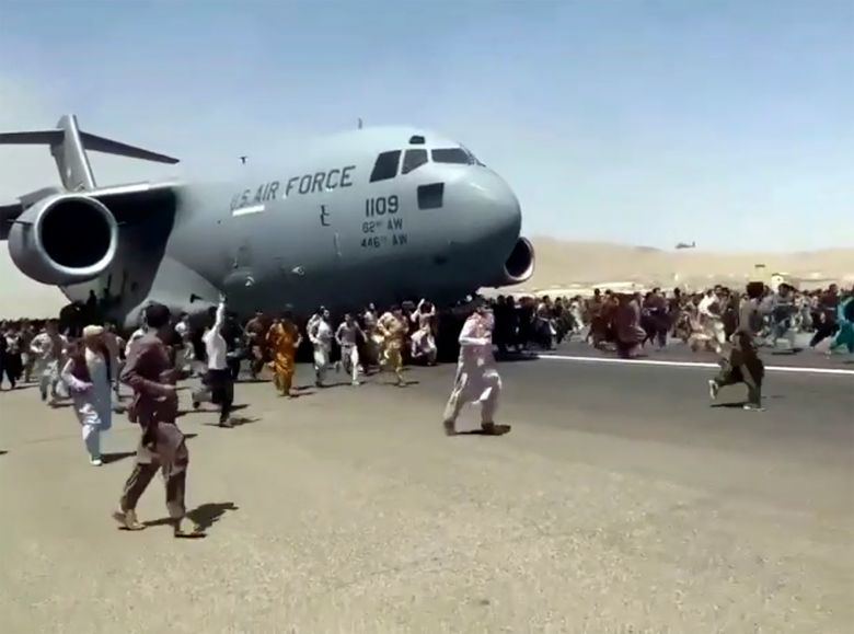FILE – In this Apug. 16, 2021 file photo, hundreds of people run alongside a U.S. Air Force C-17 transport plane as it moves down a runway of the international airport, in Kabul, Afghanistan.  Twin tragedies on opposite sides of the world are piling misery on people that have seen far more than their share. In Afghanistan, a group of gunmen known for sadistic tyranny rocketed back into power after 20 years as Western and Afghan leaders walked away with a sad shrug.(Verified UGC via AP, File)