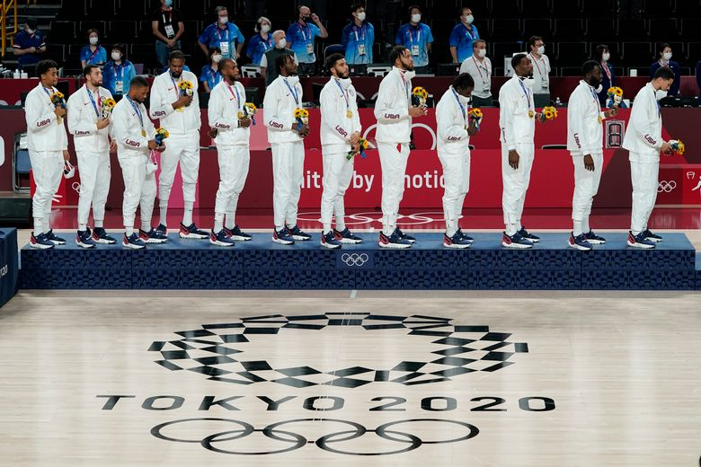 The U.S. men's basketball team stands on the podium during the national anthem after receiving their gold medals at the 2020 Summer Olympics, Saturday, Aug. 7, 2021, in Tokyo, Japan. (AP Photo/Charlie Neibergall)