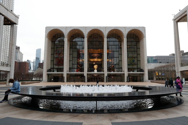 FILE – This March 12, 2020, file photo shows Josie Robertson Plaza in front of The Metropolitan Opera house, background center, at Lincoln Center in New York. The Metropolitan Opera reached a four-year agreement with the union for its orchestra, the last major deal needed for the company to resume performances following a 1 1/2-year layoff caused by the coronavirus pandemic. (AP Photo/Kathy Willens, File)