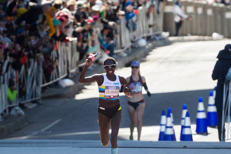 FILE – In this Feb. 29, 2020, file photo, first place finisher Aliphine Tuliamuk leads second place finisher Molly Seidel to the finish in the U.S. Olympic marathon trials in Atlanta. Tuliamuk will have company in Tokyo with her baby, Zoe, allowed to travel with her. The original plan was to start a family after the Tokyo Olympics. But when the Summer Games were postponed by the pandemic, the 32-year-old Tuliamuk and her fiance, Tim Gannon, decided not to wait. (AP Photo/John Amis, File)