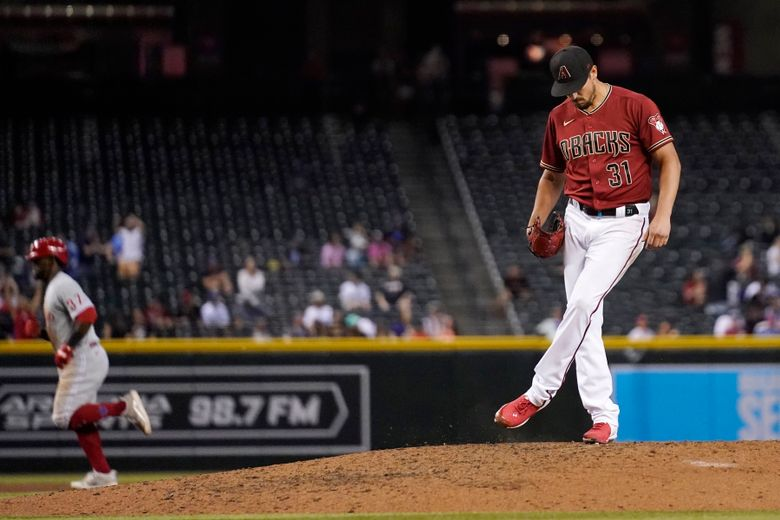 Arizona Diamondbacks relief pitcher Caleb Smith (31) kicks the dirt on the mound after giving up a home run to Philadelphia Phillies' Odubel Herrera, left, during the eighth inning of a baseball game Wednesday, Aug. 18, 2021, in Phoenix. The Diamondbacks won 4-2. (AP Photo/Ross D. Franklin)