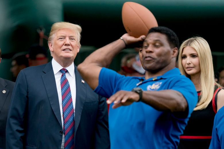 FILE – In this May 29, 2018, file photo, President Donald Trump, left, and his daughter Ivanka Trump, right, watch as former football player Herschel Walker, center, throws a football during White House Sports and Fitness Day on the South Lawn of the White House in Washington. Walker registered to vote on Tuesday, Aug. 17, 2021, in Georgia as Donald Trump has been urging the former football great to join the U.S. Senate in the state as a Republican. (AP Photo/Andrew Harnik, File)