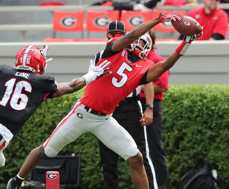 FILE – In this  Saturday, April 17, 2021 file photo, Georgia wide receiver Adonai Mitchell catches a touchdown pass past defensive back Lewis Cine during Georgia's spring NCAA college football game in Athens, Ga. They are young men who are often household names before they've done anything to warrant such attention beyond dominant high school careers. Mitchell.  made a splash with seven catches for 105 yards and a touchdown in Georgia's G-day spring game, and looked fast in the process(Curtis Compton/Atlanta Journal-Constitution via AP, File)