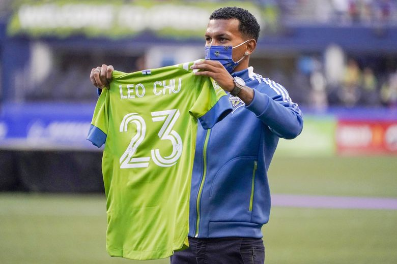 New Seattle Sounders midfielder Leo Chu displays his jersey while being introduced before the Sounders match against the Portland Timbers, Aug. 29, 2021, in Seattle. (Ted S. Warren / AP)