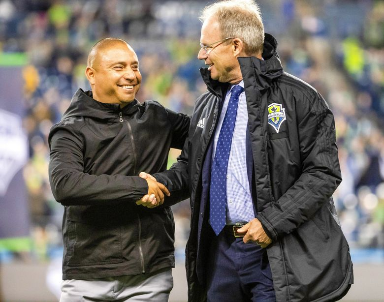 Coaches Freddy Juarez, left, and Brian Schmetzer meet before a 2019 playoff game. (Dean Rutz / The Seattle Times)
