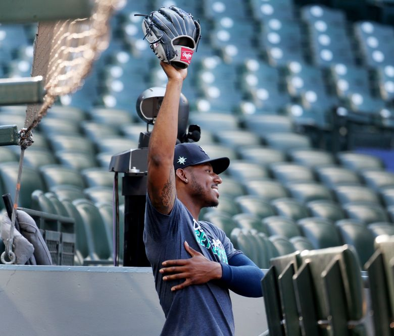 Mariners outfielder Kyle Lewis stretches in the dugout before a game in July at T-Mobile Park. (Ken Lambert / The Seattle Times)