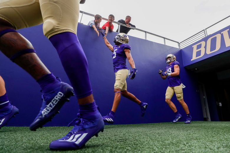 Washington Huskies defensive back Alex Cook high-fives fans as UW comes out for warm-ups before a game against the Montana Grizzlies Saturday, Sept. 4, 2021, in Seattle, Wash.  (Jennifer Buchanan / The Seattle Times)