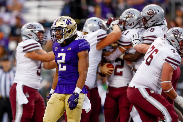 Washington Huskies defensive back Kyler Gordon walks back to the sidelines as Montana teammates mob quarterback Camron Humphrey, 2, after he scored the go-ahead touchdown during the fourth quarter Saturday, Sept. 4, 2021, in Seattle. (Jennifer Buchanan / The Seattle Times)