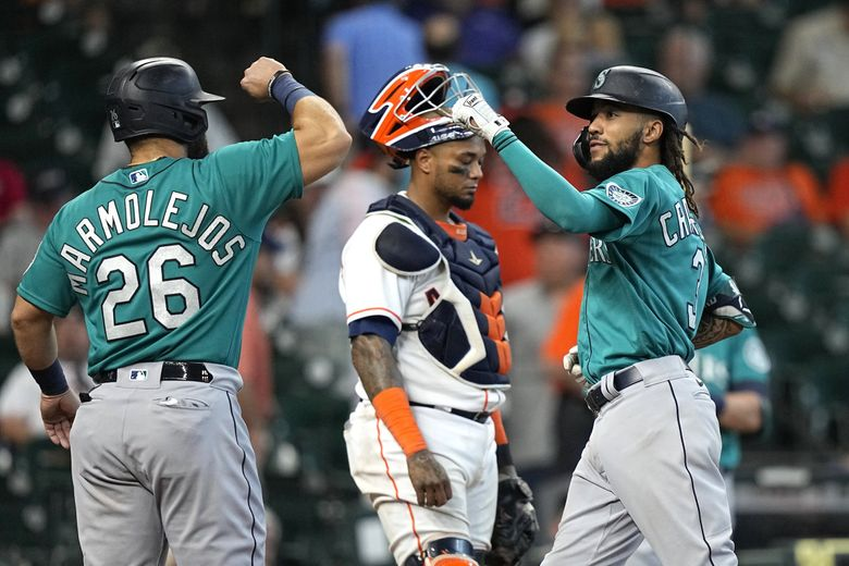 The Mariners' J.P. Crawford, right, celebrates with Jose Marmolejos after they scored on Crawford's two-run home run during the ninth inning Wednesday. (David J. Phillip / The Associated Press)