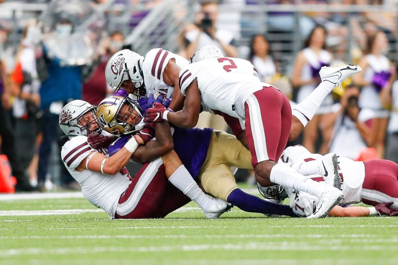 Washington Huskies wide receiver Taj Davis gets sandwiched by the Montana Grizzlies during the first quarter, Sept. 4, 2021, in Seattle. (Jennifer Buchanan / The Seattle Times)