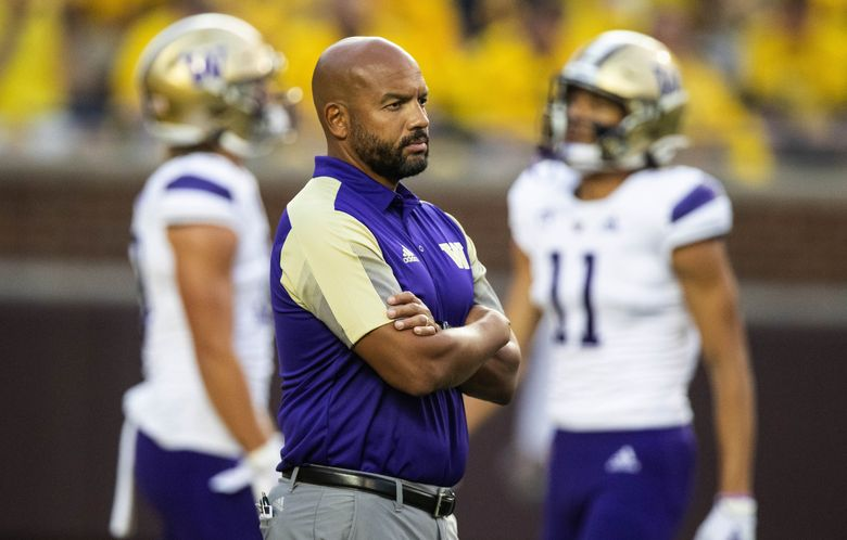 Washington coach Jimmy Lake watches his team warm up for Saturday's game at Michigan. (Dean Rutz / The Seattle Times)