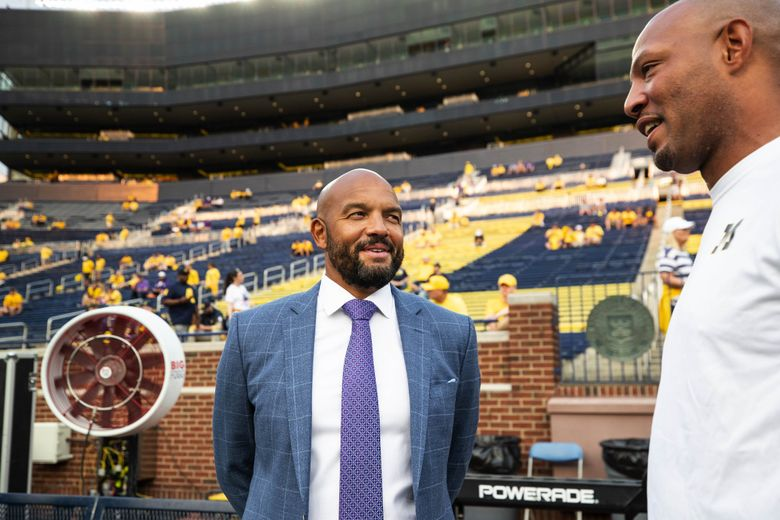 Washington coach Jimmy Lake, left, arrives for Saturday's matchup with Michigan in Ann Arbor. (Dean Rutz / The Seattle Times)