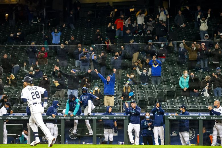 Mariners fans and players celebrate Jake Fraley's walkoff walk to end a game in the 10th inning against the San Francisco Giants, April 1, 2021 at T-Mobile Park in Seattle. (Bettina Hansen / The Seattle Times)