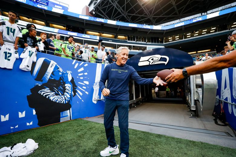 Seahawks coach Pete Carroll signs autographs for fans before the start of a preseason game against the Denver Broncos on Aug. 21, 2021, in Seattle. (Jennifer Buchanan / The Seattle Times)