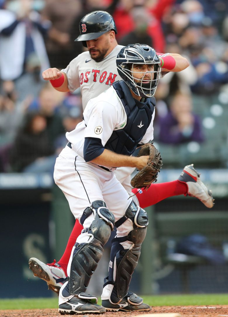 Mariners catcher Tom Murphy waits for the ball as Red Sox left fielder Kyle Schwarber scores a sixth run in the 10th inning, Wednesday, Sept. 15, 2021 in Seattle. (Ken Lambert / The Seattle Times)