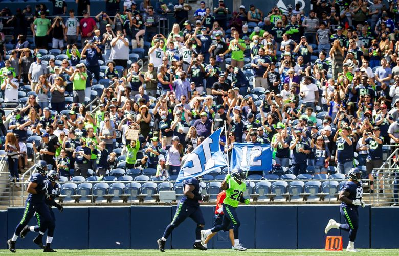 Seahawks cornerback Ugo Amadi carries the 12 flag out to cheering fans before a mock game Aug. 8 at Lumen Field. (Bettina Hansen / The Seattle Times)