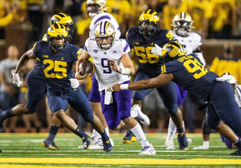 With no place else to go, Dylan Morris runs the ball up the middle in a game against the Michigan Wolverines, Sept. 11, 2021 at Michigan Stadium, in Ann Arbor. (Dean Rutz / The Seattle Times)
