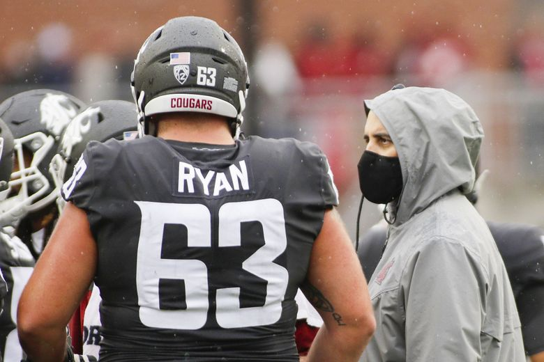 Washington State head coach Nick Rolovich, right, speaks with offensive lineman Liam Ryan during a break in the first half against Southern California, Saturday, Sept. 18, 2021, in Pullman, Wash. (Young Kwak / AP)