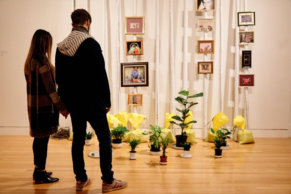 """Visitors to the Frye Art Museum view Duane Linklater's """"action at a distance,"""" created from painted teepee poles, nylon rope, plants, ceramics, sandbags, 12 framed digital prints and framed mirror. (Jonathan Vanderweit)"""