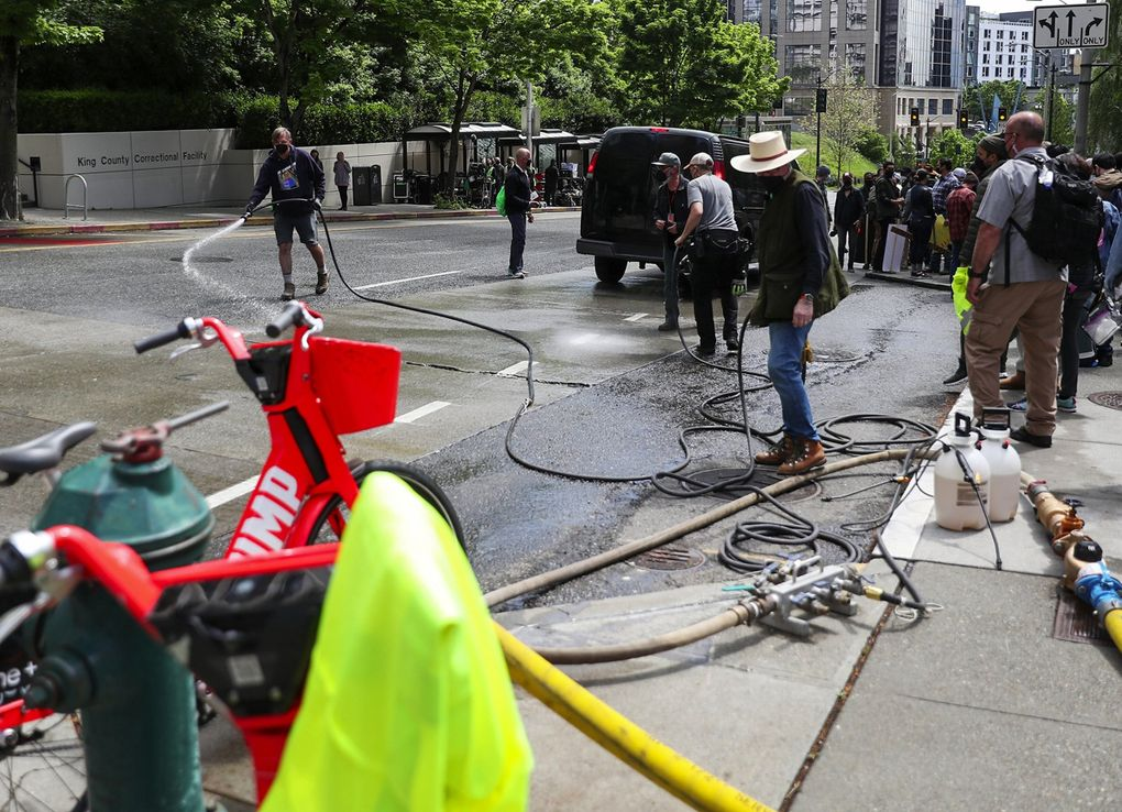 """On a sunny spring day, Fifth Avenue near James Street is hosed down to make Seattle appear more stereotypically damp for cameras for the movie """"Kimi."""" (Ken Lambert / The Seattle Times)"""