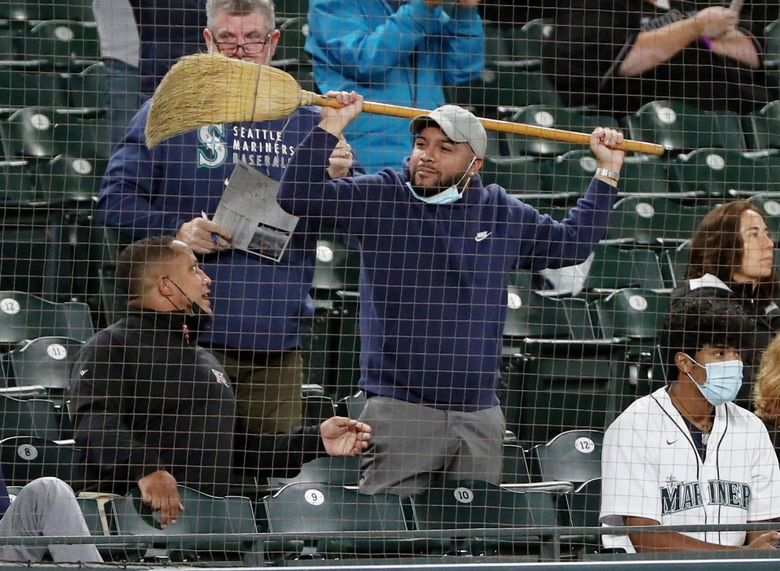 A fan with a broom is seen as the Mariners head into the ninth inning against Oakland, Sept. 27, 2021 in Seattle. The M's won 13-4. (Ken Lambert / The Seattle Times)