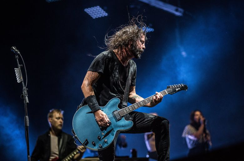 Foo Fighters frontman and former Nirvana member Dave Grohl performs with the rest of the band during a  concert at Safeco Field in 2018. Foo Fighters and Death Cab for Cutie are set to play Climate Pledge Arena's first concert — a benefit show — on Oct. 19. (Rebekah Welch / The Seattle Times)