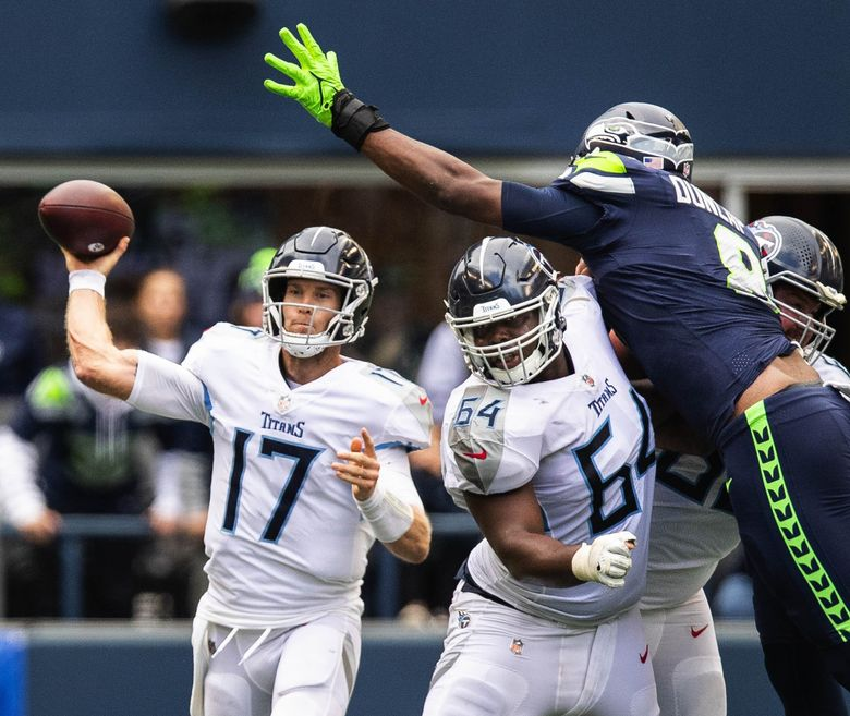 In overtime, Ryan Tannehill finds an open receiver and moves the ball downfield as Seattle's Carlos Dunlap is stood up by Tennessee guard Nate Davis. (Dean Rutz / The Seattle Times)