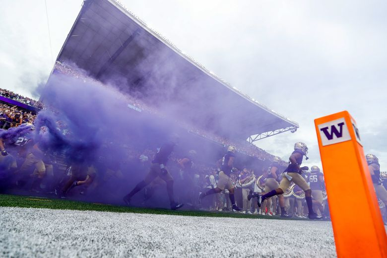 The Washington Huskies run out onto the field before the start of a game against the Montana Grizzlies Saturday, Sept. 4, 2021, in Seattle, Wash.(Jennifer Buchanan / The Seattle Times)
