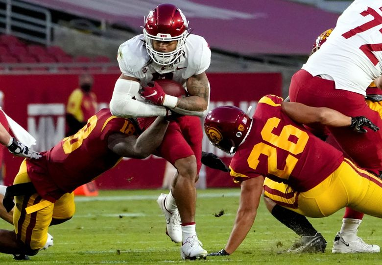 Washington State running back Deon McIntosh, center, runs out of the grasp of Southern California linebacker Raymond Scott , left, and past linebacker Kana'i Mauga (26) during the first half of an NCAA college football game in Los Angeles, Sunday, Dec. 6, 2020. (Alex Gallardo / AP)