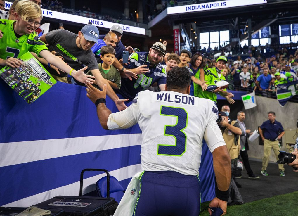 Russell Wilson celebrates with the 12s at Lucas Oil Stadium after Seattle's 28-16 win over Indianapolis Sunday. (Dean Rutz / The Seattle Times)